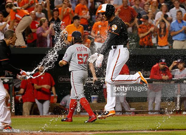 Manny Machado sprays Jonathan Schoop of the Baltimore Orioles with water after Schoop hit a walk off home run in the ninth inning to give the Orioles...