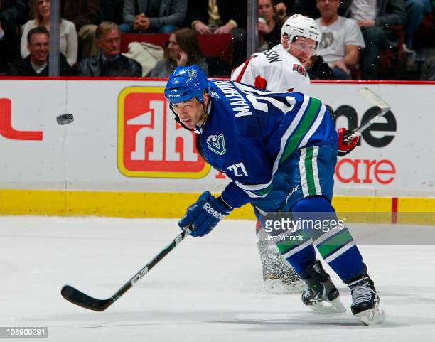 Manny Malhotra of the Vancouver Canucks and Daniel Alfredsson of the Ottawa Senators watch a loose puck during their game at Rogers Arena on February...