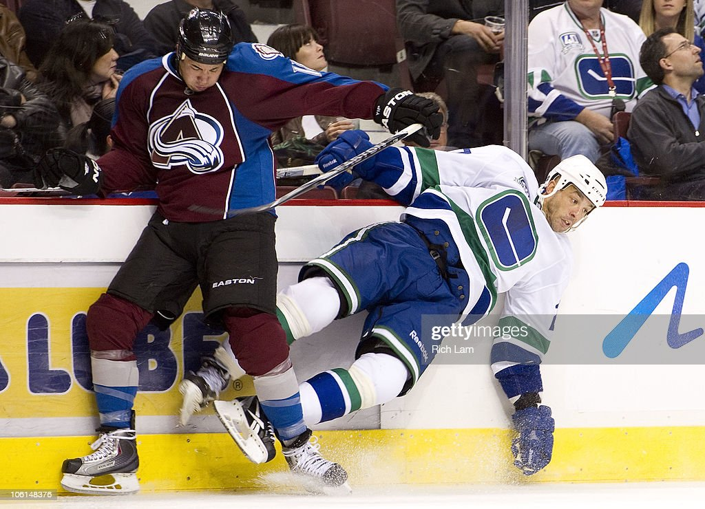 Manny Malhotra #27 of the Vancouver Canucks gets knocked down by a hit from Brandon Yip #18 of the Colorado Avalanche during the third period in NHL action on October 26, 2010 at Rogers Arena in Vancouver, British Columbia, Canada.