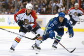 Manny Malhotra of the Vancouver Canucks tries to check Stephen Weiss of the Florida Panthers during the third period in NHL action on October 11 2010...