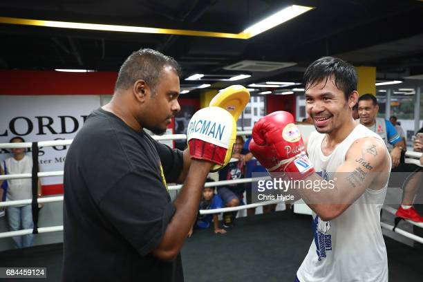 Manny Pacquiao hits the pads with Australian journalist Jamie Pandaram during a training session at the Elorde boxing Gym on May 19 2017 in Manila...