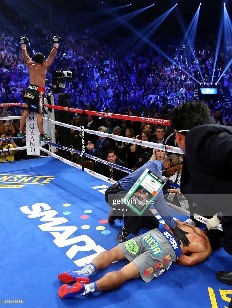 Manny Pacquiao lays face down on the mat after being knocked out in the sixth round as Juan Manuel Marquez celebrates during their welterweight bout at the MGM Grand Garden Arena on December 8, 2012 in Las Vegas, Nevada.