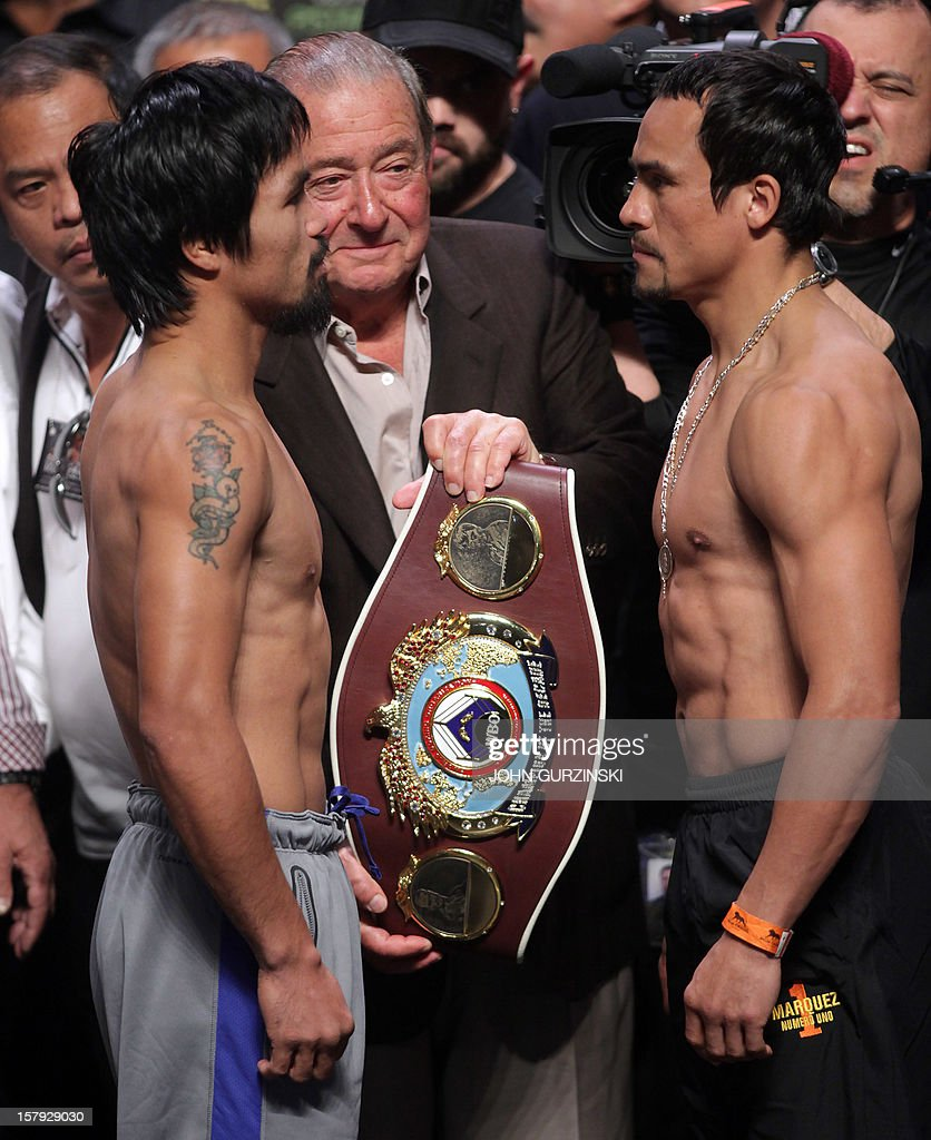 Manny Pacquiao (L) of the Philippines and Juan Manuel Marquez (R) of Mexico pose as boxing promoter Bob Arrum (C) holds the WBO belt during their weigh-in December 7, 2012 in Las Vegas, Nevada. Filipino southpaw Pacquiao needs a statement victory over Marquez in the fourth installment of their epic rivalry December 8, 2012 to prove once and for all who is the better fighter. AFP PHOTO / John GURZINSKI