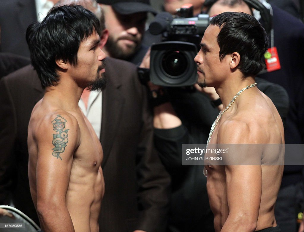 Manny Pacquiao (L) of the Philippines faces Juan Manuel Marquez (R) of Mexico during their weigh-in December 7, 2012 in Las Vegas, Nevada. Filipino southpaw Pacquiao needs a statement victory over Marquez in the fourth installment of their epic rivalry December 8, 2012 to prove once and for all who is the better fighter. AFP PHOTO / John GURZINSKI