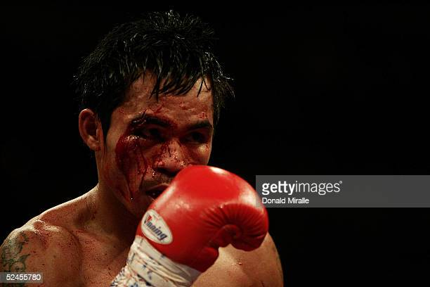 Manny Pacquiao of the Philippines is shown with a cut above his right eye inflicted by Erik Morales of Mexico during the World Super Featherweight...