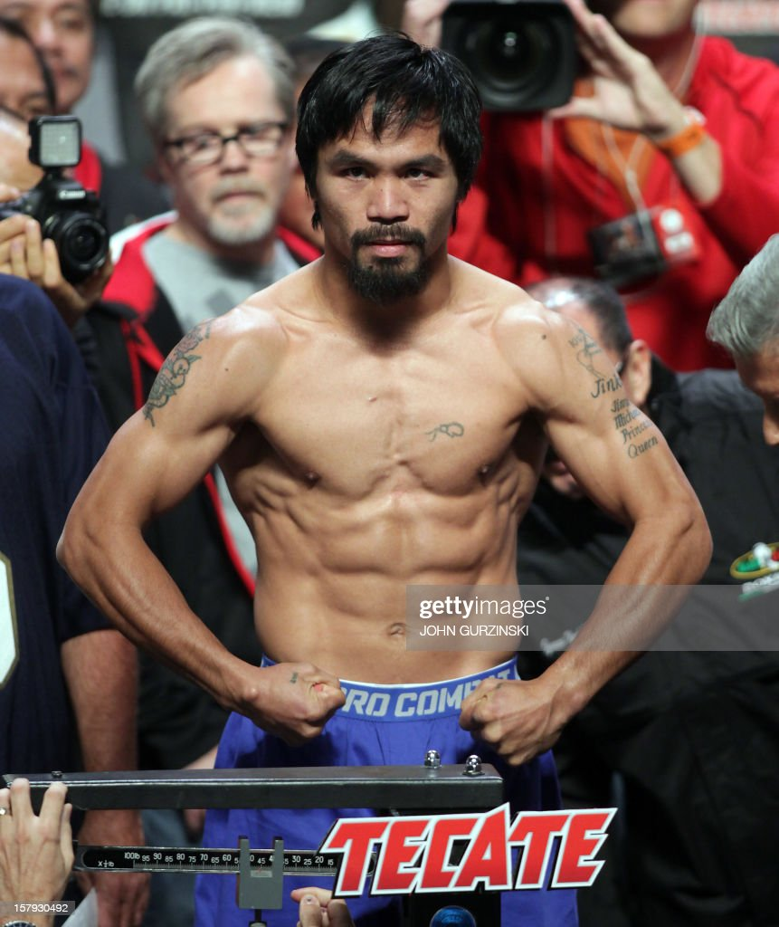 Manny Pacquiao of the Philippines poses during his weigh-in with Juan Manuel Marquez of Mexico (out of frame) December 7, 2012 in Las Vegas, Nevada. Filipino southpaw Pacquiao needs a statement victory over Marquez in the fourth installment of their epic rivalry December 8, 2012 to prove once and for all who is the better fighter. AFP PHOTO / John GURZINSKI