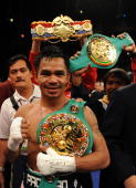 Manny Pacquiao of the Philippines poses with his belts after he knocks out David Diaz during the ninth round of the WBC Lightweight Championship at...