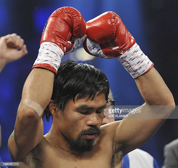 Manny Pacquiao of the Philippines raises his gloved fists prior to the start of his WBO welterweight title fight against Timothy Bradley of the US at...