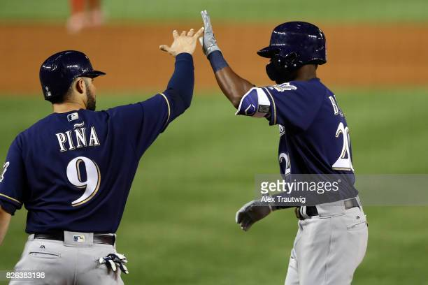 Manny Pina and Lewis Brinson of the Milwaukee Brewers celebrate after scoring during the game against the Washington Nationals at Nationals Park on...