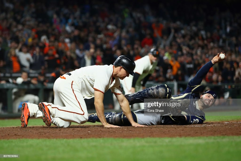 Manny Pina #9 of the Milwaukee Brewers shows that he held on to the ball after he tagged out Nick Hundley #5 of the San Francisco Giants at home plate in the eighth inning at AT&T Park on August 22, 2017 in San Francisco, California.