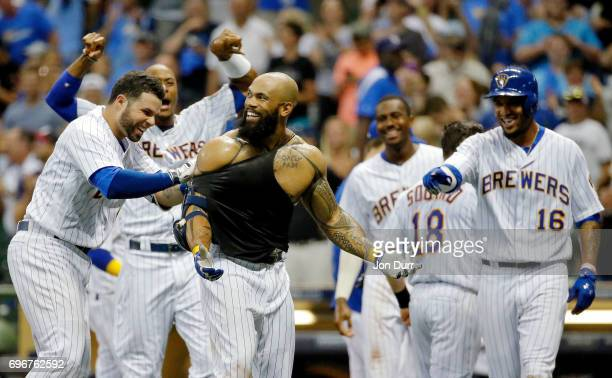Manny Pina of the Milwaukee Brewers tries to rip off the shirt of Eric Thames after he hit a walkoff home run against the San Diego Padres during the...