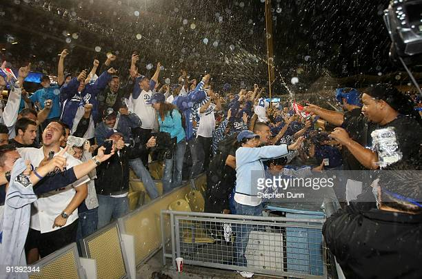 Manny Ramirez of the Los Angeles Dodgers and teammates spray champagne on fans as they celebrate after the game with the Colorado Rockies on October...