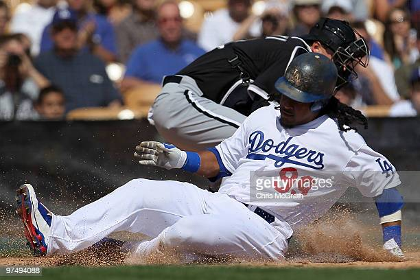 Manny Ramirez of the Los Angeles Dodgers slides home to score off a single by teammate Casey Blake against the Chicago White Sox during a spring...