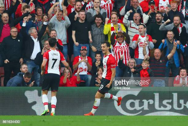Manolo Gabbiadini of Southampton celebrates as he scores their second goal from the penalty spot with Shane Long and fans during the Premier League...