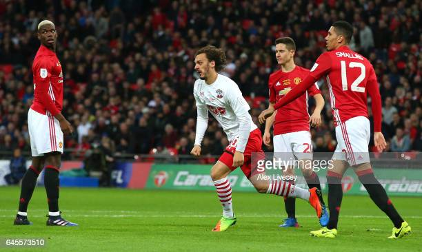 Manolo Gabbiadini of Southampton celebrates as Paul Pogba Ander Herrera and Chris Smalling of Manchester United look dejected as he scores their...