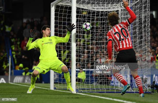 Manolo Gabbiadini of Southampton shoots at Thibaut Courtois of Chelsea during the Premier League match between Chelsea and Southampton at Stamford...