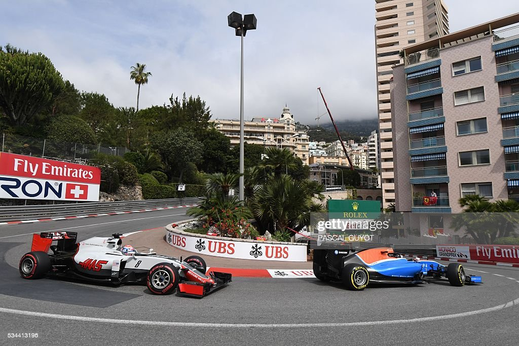 Manor's Racing's German driver Pascal Wehrlein and HAAS F1 (R) and Team's French driver Romain Grosjean (L) drive during the first practice session at the Monaco street circuit, on May 26, 2016 in Monaco, three days ahead of the Monaco Formula 1 Grand Prix. / AFP / PASCAL