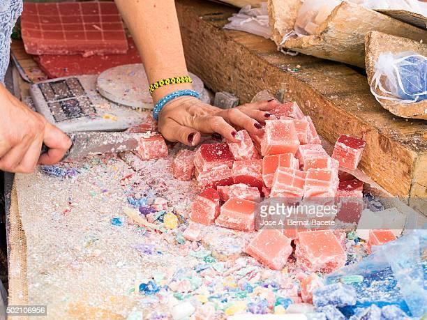 Manos de una mujer cortando jabon artesanal en trozos