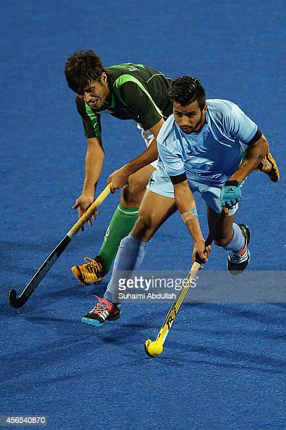 Manpreet Singh of India and Muhammad SR Rizwan of Pakistan challenge for the ball during the menÕs hockey gold medal match on day thirteen of the...