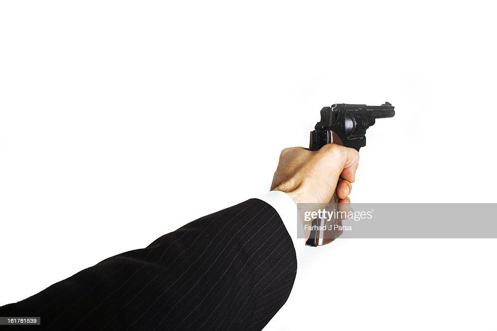 Man's arm, wearing suit, points handgun away. : Stock Photo