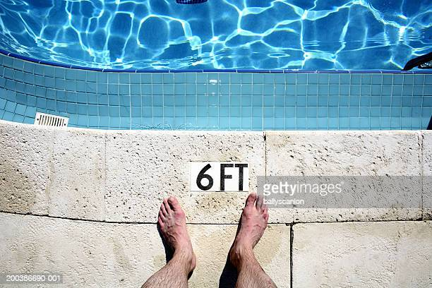 Man's bare feet beside pool, low section, overhead view
