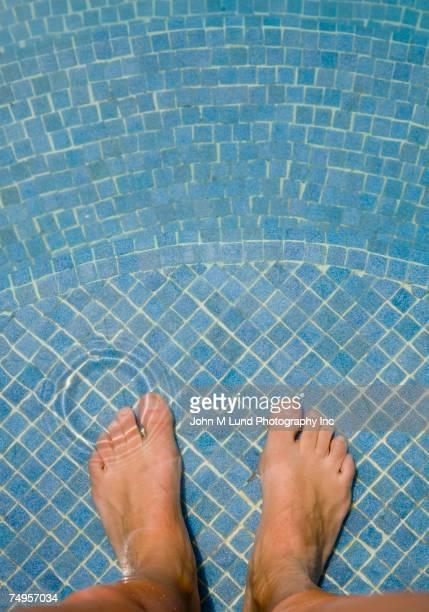 Man's bare feet in swimming pool