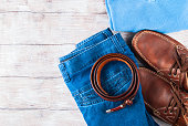 Man's clothes flat lay with blue jeans, T-shirt, pullover, leather shoes and belt