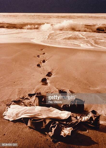 Man's clothing on beach, footprints leading into sea (toned B&W)