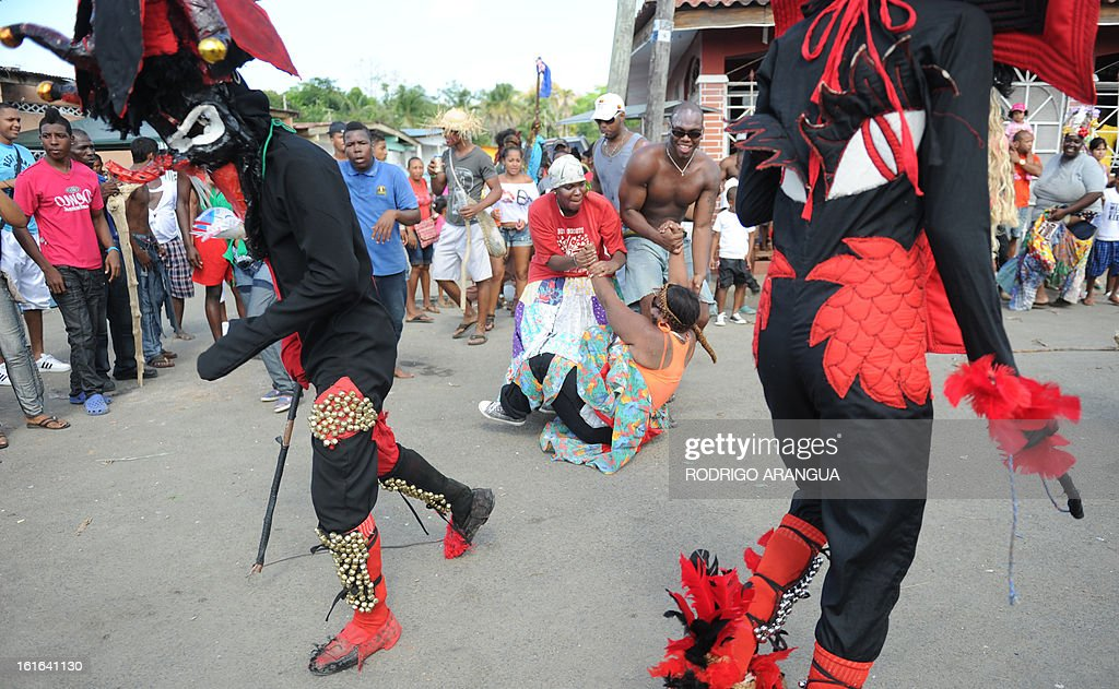 A mans disguised as the devil confronts a pedestrian during the so called 'Congos y Diablo', Congos and Devil, carnival ritual in Nombre de Dios 120 km north to Panama City on February 13, 2013 . The celebration dates to colonial times with devils representing the Spanish conquerors and the 'Congos' African slaves. AFP PHOTO/ Rodrigo ARANGUA