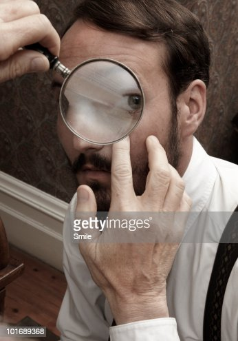 Man's eye being examined with a magnifying-glass : Stock Photo