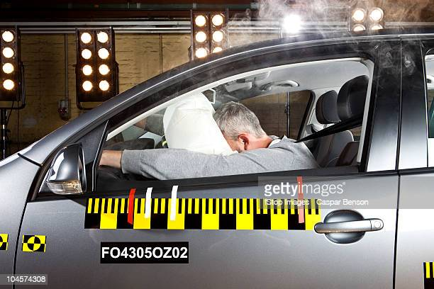 A man's face impacting an airbag in a crash test car