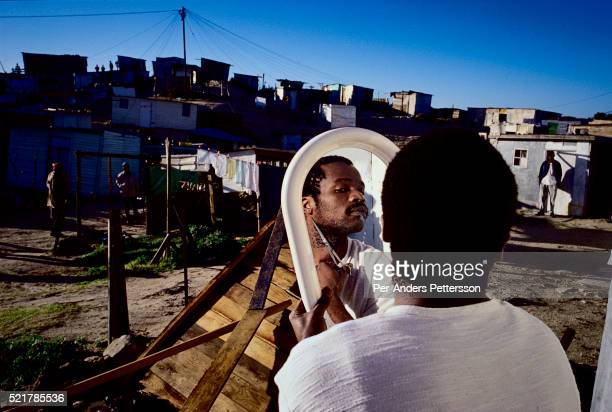 A mans face is reflected in a mirror as he cuts his beard outside his house in Khayelitsha the biggest black township outside Cape Town South Africa