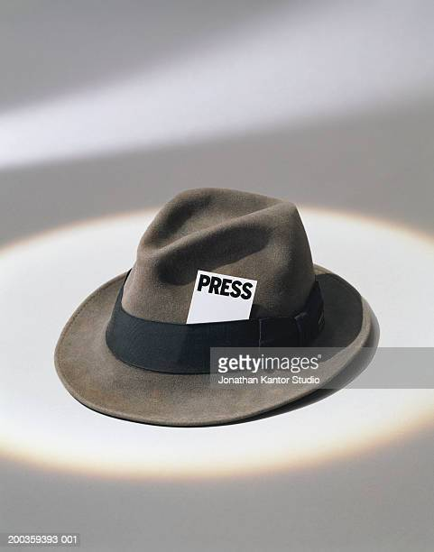 Man's fedora with press card