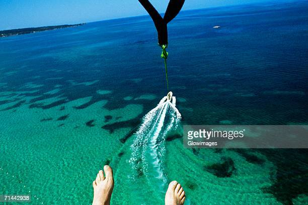 A mans feet are seen as he parasail over Negril Beach, Jamaica