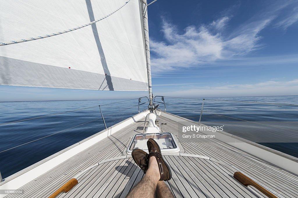 Man's feet crossed on 62 ft sailboat : Stock Photo