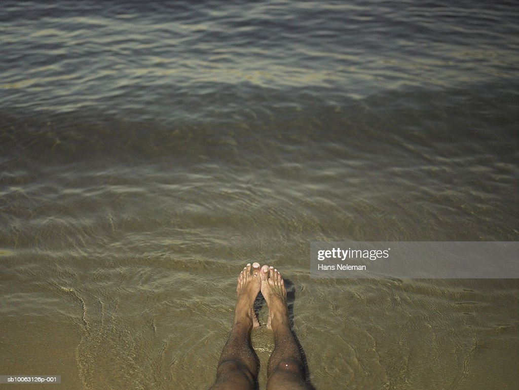Man's feet in sea, low section : Stock Photo