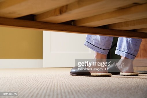 Man's feet in slippers next to bed