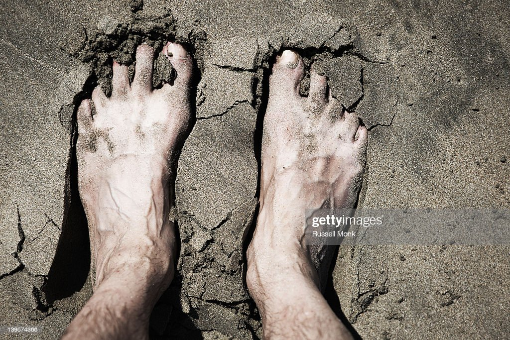 Man's feet in the wet sand. : Stock Photo