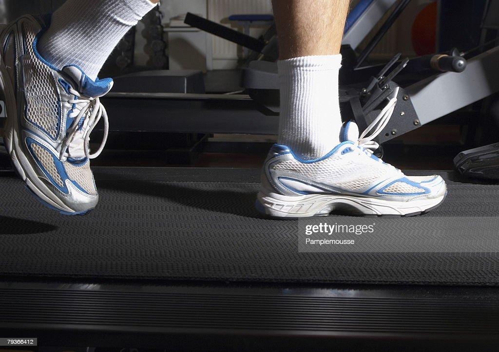 Man's feet on a treadmill in a gym : Stock Photo