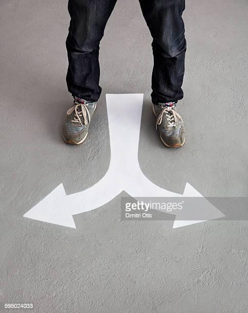 Mans feet standing in front of arrow floor marking