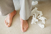 Man's feet surrounded by crumpled tissues