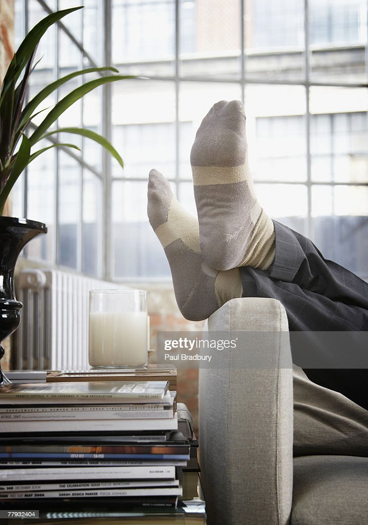 Man's feet up on arm of couch in modern home : Stock Photo