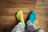 View of mans feet wearing mis matched coloured socks.