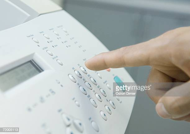 Man's finger about to push button on fax machine