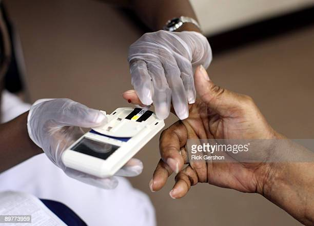 A mans finger is pricked to test his cholesterol at the City of Newark's free homeless health fair at the Department of Child and Family WellBeing on...