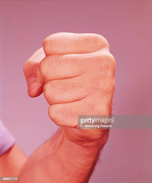 Man's fist against blue background