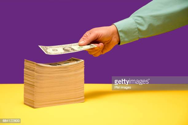 Man's hand adding dollar to a pile of dollars