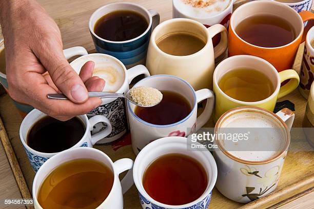 Man's hand adding sugar to a cup of tea