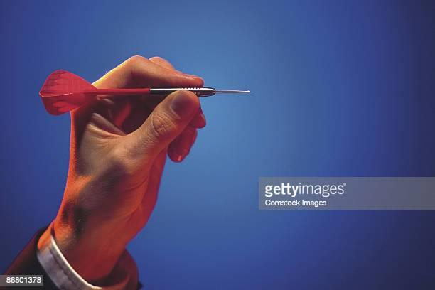 Man's hand aiming dart