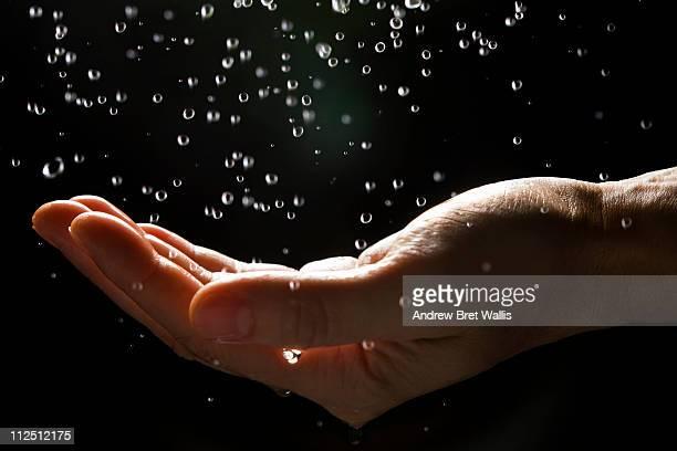 Man's hand catching falling rain drops